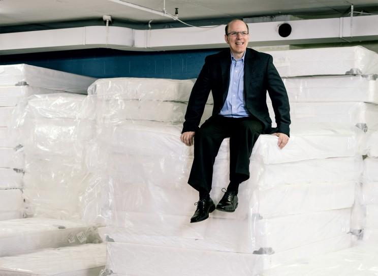 Man sitting on large stacks of mattresses