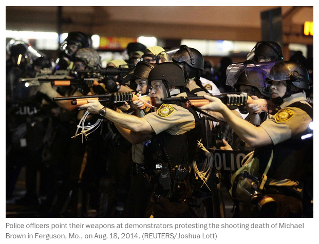 Police officers point weapons at demonstrators in Ferguson, MO