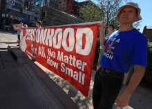 "Man holding banner that says ""Personhood For All No Matter How Small"""