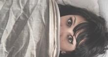 Woman hiding under bedsheet