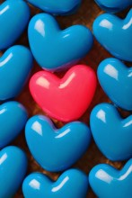 One Red heart-shaped bead surrounded by Blue heart-shaped beads